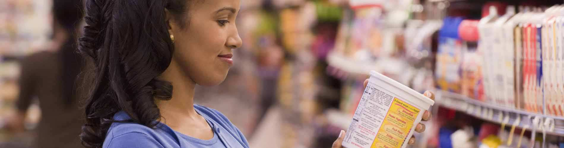 woman looking at items on grocery store shelves