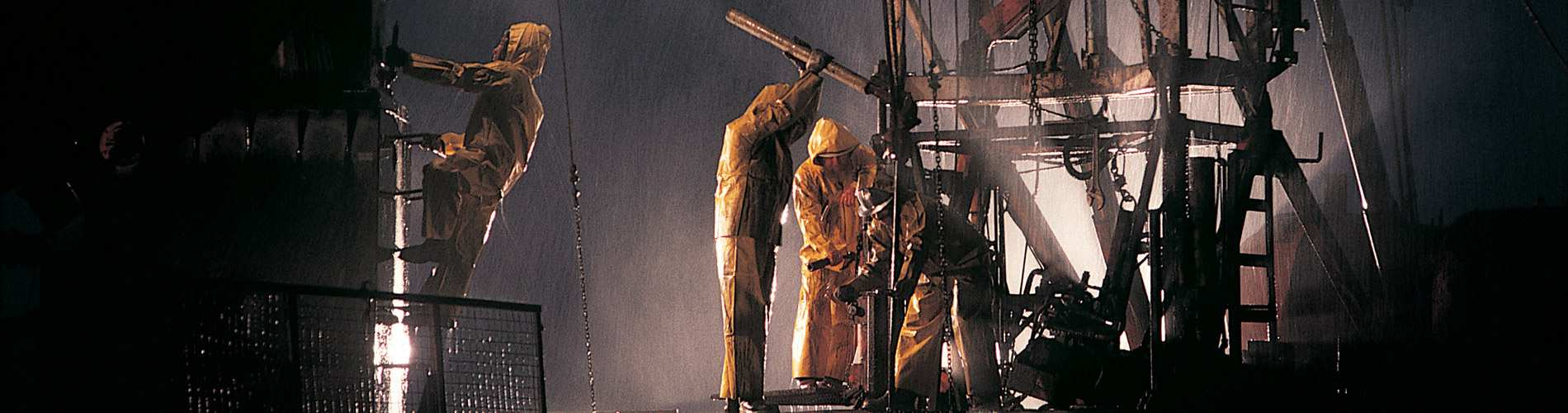 Technicians working outside in the rain on oil rig.
