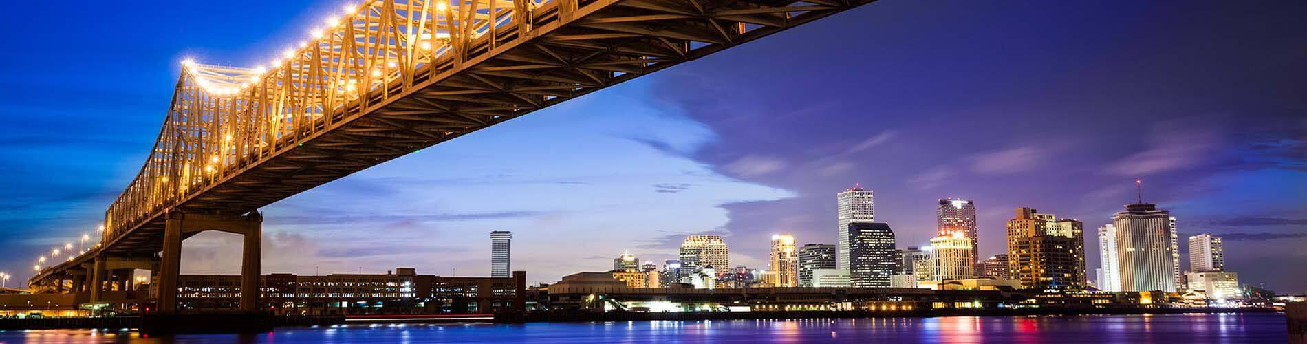 city scene of New Orleans showing water, skyline and a bridge