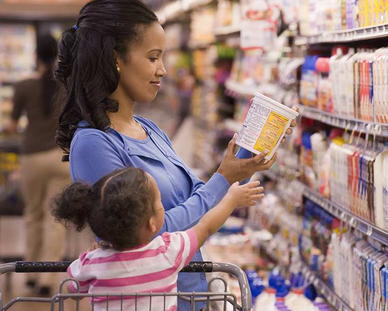 Small child with mother in grocery store.