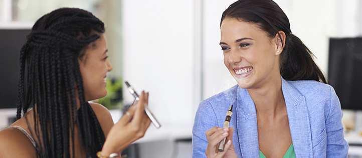 Two females smoking e-cigarettes.