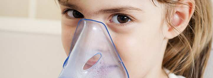 Young girl with inhaler mask