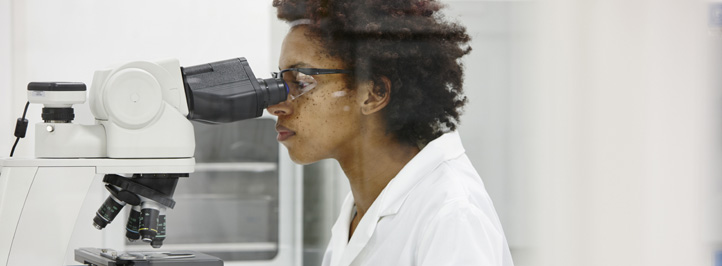 researcher looking through a microscope
