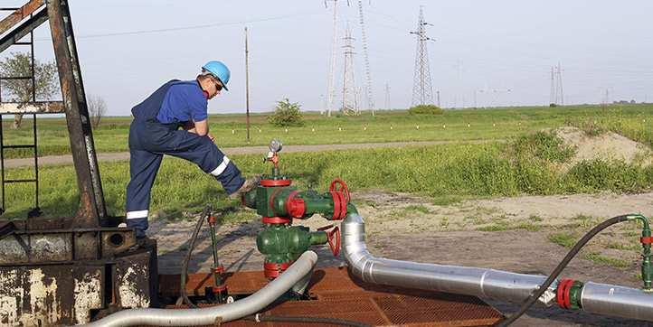 Male technician standing on oil pipe.
