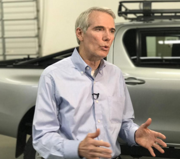 Photo: Senator Rob Portman speaking in front of a Battelle Armored Commercial Vehicle